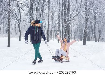 Happy winter couple. Man sledding on sled woman on winter vacation in snowy forest. Fun couple playful together outdoor. People, winter season, leisure and love concept