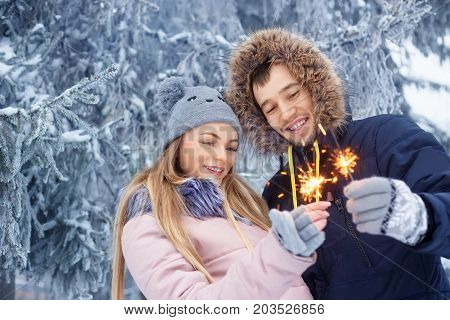young couple with sparklers in winter forest. Smiling family with bengal lights. Happy smiling couple with holiday sparklers celebrating Christmas outdoors