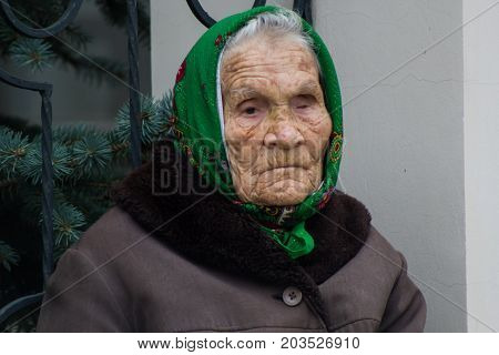 KAZAN, RUSSIA - September 5, 2017: Elderly grandmother with defect of vision near Orthodox Church, telephoto shot