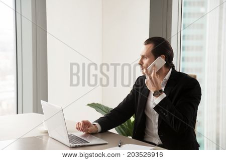Concerned serious handsome young businessman in modern office sitting at the desk, working on laptop computer, making phone call. Making important decision, concerned about deadline, planning meeting.