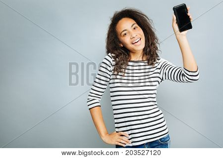 New phone model. Positive woman keeping smile on her face and bowing head while putting hand on the belt