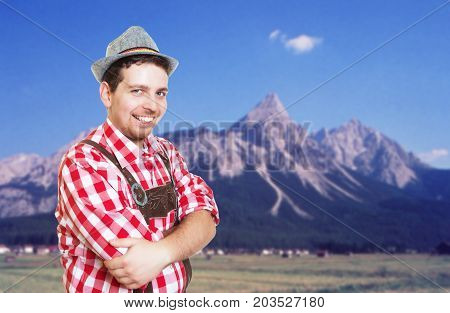 Bavarian man with leather pants and hat is ready for the oktoberfest and mountains in the background