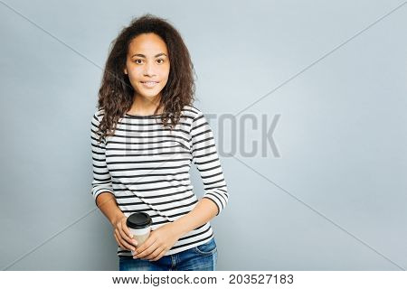 Lets go for a walk. Charming mulatto keeping smile on her face and looking forward while standing isolated on grey background