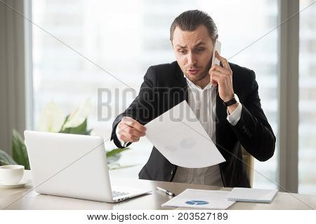 Shocked mad businessman in modern office talks on the phone holding financial report document, wrinkling his forehead in concern. Failing profit statistics, loss in stock market, bad decision concept.