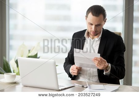 Young handsome businessman reading important financial letter at workplace in modern office. Laptop, notes, cup of coffee on the table. Business proposal concept, work correspondence, bill concept.