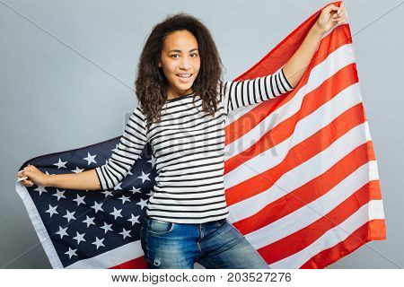 My flag. Delighted young woman looking at camera and stretching arms while expressing positivity