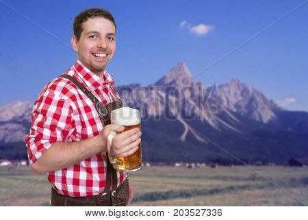 Happy bavarian oktoberfest guest with leather pants and beer mug and mountains in the background