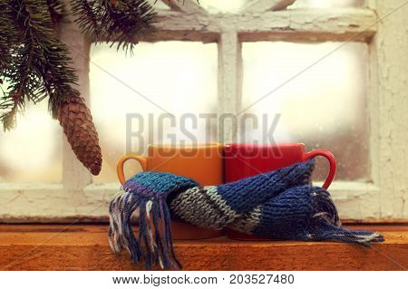 two mugs in scarf on the background of a fir branch and an old window morning / warming atmosphere of a winter vacation