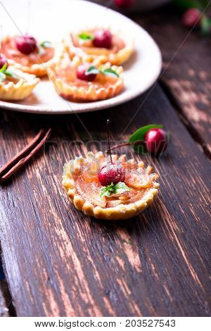 Apple Caramel Little Tarts On White Plate And Brown Rustic Background. French Tatin With Paradise Ap