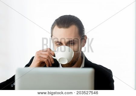 Close up portrait of relaxed businessman looking at laptop screen and drinking coffee in modern office setting. Young project manager taking break from heavy workload. Isolated on white background.
