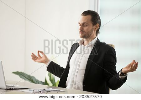 Calm young handsome businessman meditating in yoga pose in front of laptop at workplace in modern office setting. Reducing discomfort, getting ready for important meeting, relieving stress concept.