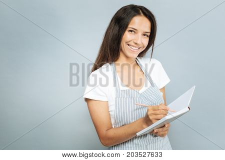 Dictate me. Good looking brunette keeping smile on face and posing on camera while being in striped apron
