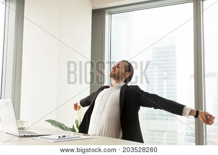 Smiling businessman stretching his back and arms at the desk at workplace in modern office with window behind. Taking a break from workflow, relaxing, being done with work, finished project concept.
