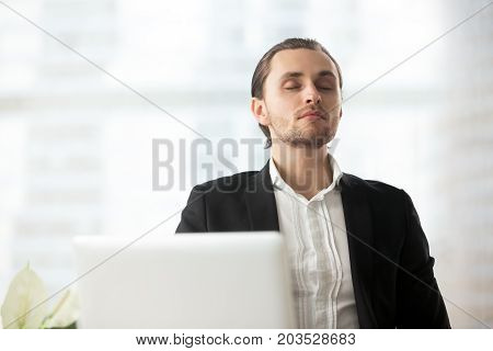 Young calm handsome businessman resting at workplace with eyes closed. Relaxation during workflow, meditation before important meeting, wellness and stress relief at work, maintaining focus concept.