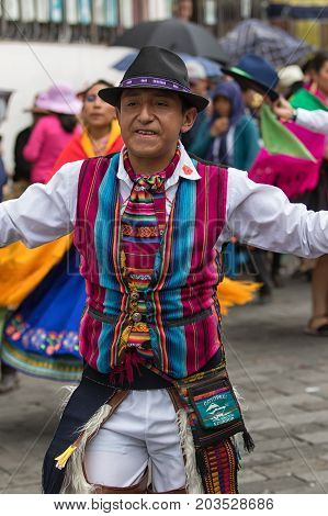 June 17 2017 Pujili Ecuador: indigenous quechua man in traditional wear performing a dance during Corpus Christi parade in the high altitude Andean town