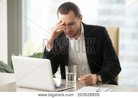Stressed businessman having severe headache, holding painkiller remedy pill. Sick CEO with head cold, thinking about taking medicine with glass of water. Being ill at work, stress induced migraine.