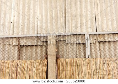 Light Gray Brown Wall With Slate Boards And Wire Fence