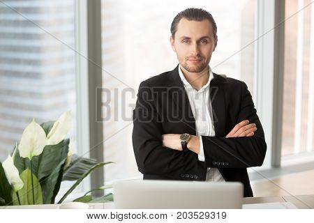 Portrait of young smiling successful businessman or entrepreneur.  Handsome young project manager, ambitious CEO posing for camera with arms crossed on chest, corporate representative at workplace.