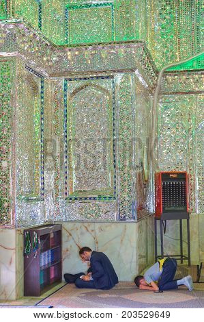 Fars Province Shiraz Iran - 18 april 2017: Mirrored mausoleum in Sayyed Alaeddin Hossein Mosque Muslims pray and read the Koran.