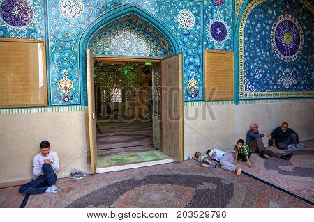 Fars Province Shiraz Iran - 18 april 2017: Mirrored mausoleum and Mosque of Sayyed Alaeddin Hossein Muslim parishioners sit in front of the entrance.