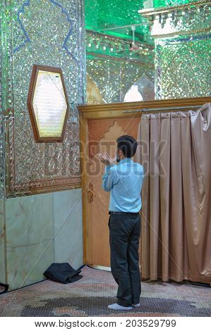 Fars Province Shiraz Iran - 18 april 2017: Interior of Sayyed Alaeddin Hossein Mosque one Muslim parishioner prays to the holy place.