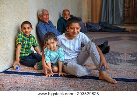 Fars Province Shiraz Iran - 18 april 2017: Group portrait of Iranian children sitting on the carpet in front of the mosque.