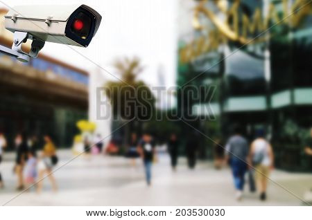CCTV security outdoor camera system operating with blurred image of people walking at department store shopping mall surveillance security and safety technology concept