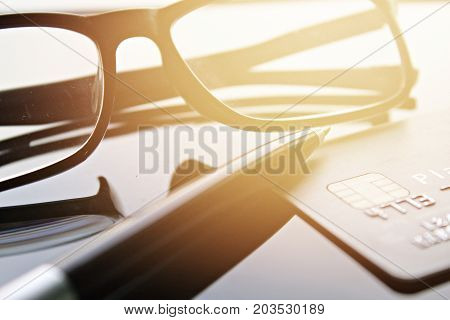 Business, finance, credit card, shopping, saving money, banking, loan, investment, taxes or accounting concept : Credit card, eyeglasses and pen on office desk table