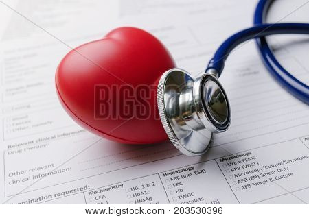 close up stethoscope red heart and patient information form on desk heart attack heart disease medical diagnosis medical report record and history patient concept selective and soft focus