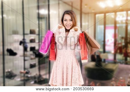 cheerful young asian woman happy smiling holding shopping bags while standing at trendy shoes shop in department store shopping mall online payment shopping online lifestyle technology concept