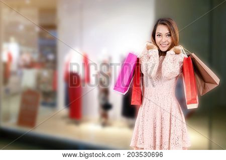cheerful young asian woman happy smiling holding shopping bags while standing at trendy clothes shop in department store shopping mall online payment shopping online lifestyle technology concept