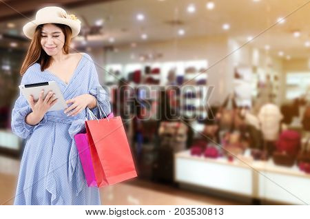 cheerful young asian woman watching special offer in mobile tablet and holding shopping bag while standing at trendy bag shop in department store shopping mall online payment shopping online concept