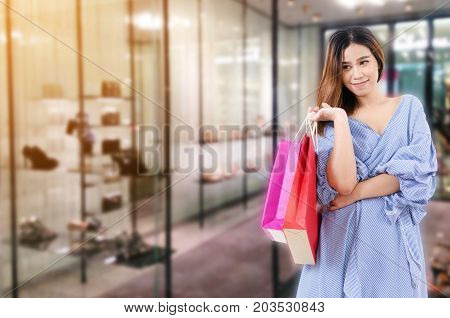 cheerful young asian woman holding shopping bags while standing at trendy shoes shop in department store shopping mall online payment shopping online lifestyle technology concept