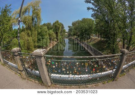 TIMISOARA ROMANIA - AUGUST 30 2017: Bridge with lovers locks symbol of loyalty and eternal love over the Bega River in Timisoara.