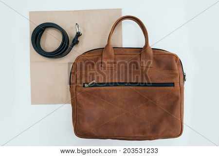 Men's accessories. The leather belt and a bag lying on a table. White background