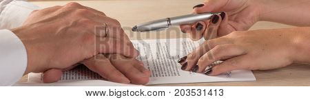 Hands of contractual parties, a woman and a man, signing a contract: business, premarital, loan, mortgage, credit, sales and purchase, investment agreement, divorce documents or other papers