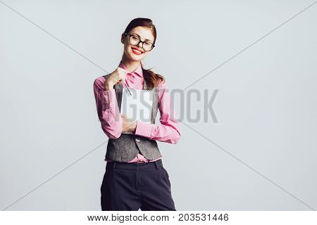 Woman teacher with glasses smiling, looking at camera. Isolated on a gray background
