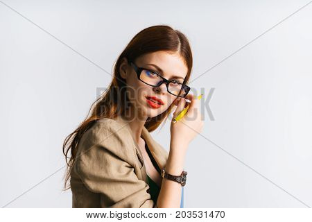 A woman teacher wearing glasses looks at the camera holding a yellow pen in her hands. The clock is on hand