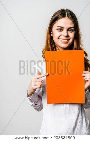 Smiling girl looking at camera holding an orange folder. She points her finger at the folder