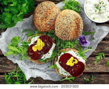 Rustic wholegrain buns with cottage cheese, rocket leaves, beetroot slices and edible viola flowers. Vegetarian food snack