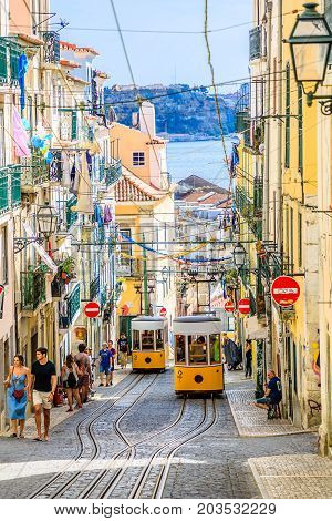 Lisbon, Portugal - August 26, 2017: intersection point of two Bica Funicular. The Elevador or Ascensor da Bica is a popular tourist attraction in Chiado District, Lisbon. Tagus river on background.