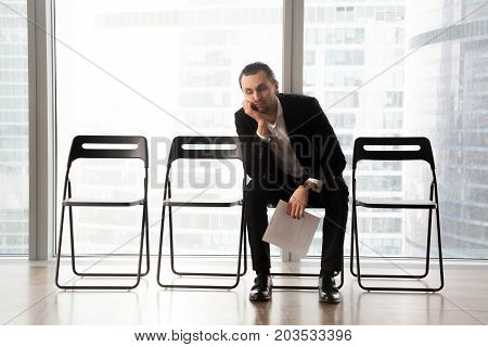 Bored young man in formal suit sitting on office chair in waiting room with document or resume in hand. Young job candidate or businessman waiting too long for interview or business meeting to start.
