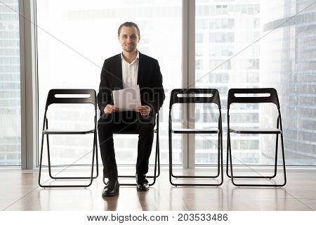 Ambitious smiling young man holds resume or positive business project result, sitting in waiting room. Candidate hopes he will get hired, entrepreneur confident his business plan is successful.