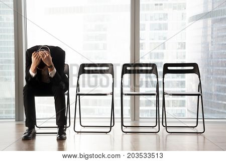 Stressed upset businessman sitting on chair, in waiting room, received bad news. Devastated CEO fired by his boss because of failed business project. Job candidate received refusal from HR department.