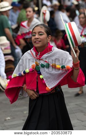June 17 2017 Pujili Ecuador: young kichwa woman in traditional clothing performing street dance at the annual Corpus Christi festival in the Andean town