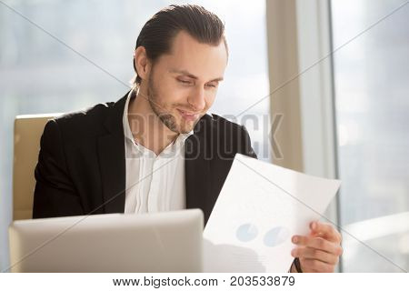 Young handsome smiling business man sitting in modern office holding financial report document, entrepreneur or CEO pleased with promising successful stock investment profit. Finance success concept.