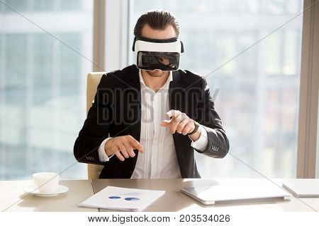 Businessman in vr headset goggles working in augmented reality at workplace. Young office worker or entrepreneur immersed in virtual reality, using innovative technology, managing business projects.