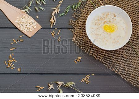 Porridge from oat flakes in a white dish, healthy Breakfast, on wooden table, top view, with natural grain, spikelets and cereals oats,