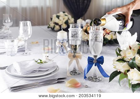 Two glasses of champagne on the background of the wedding bouquet of pink roses.