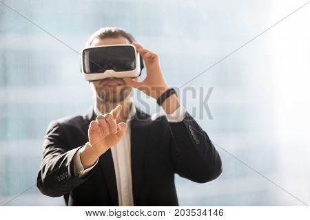 Smiling businessman in VR glasses pointing finger in air. Office worker or CEO immersed in virtual reality, innovative method of browsing web or managing business project through augmented reality.